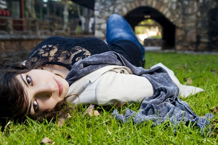 lies down: Beautiful young girl lies down on the green grass on a urban park. Stock Photo
