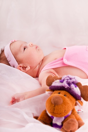 View of a newborn baby on smooth bed with toy. photo