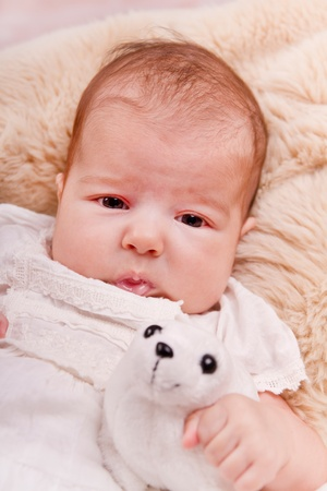 View of a newborn baby on a smooth bed with toy. photo