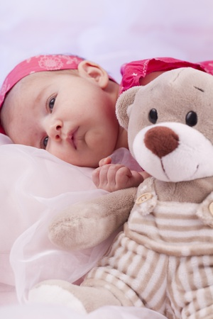 View of a newborn baby on smooth bed with stuffed toy. photo