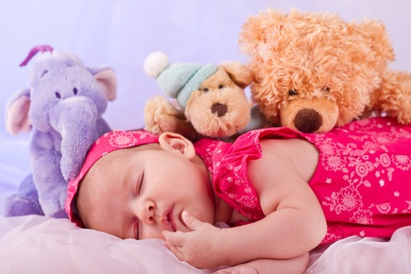 cute girl with teddy bear: View of a newborn baby on smooth bed with stuffed toy sleeping. Stock Photo