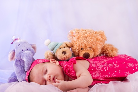 beautiful bed: View of a newborn baby on smooth bed with stuffed toy sleeping. Stock Photo