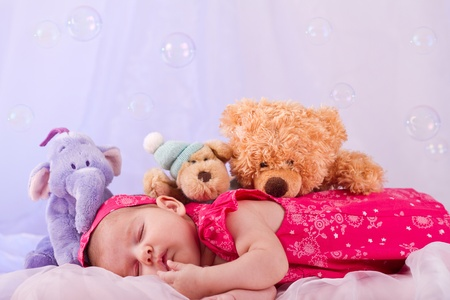 View of a newborn baby on smooth bed with stuffed toy sleeping. Foto de archivo