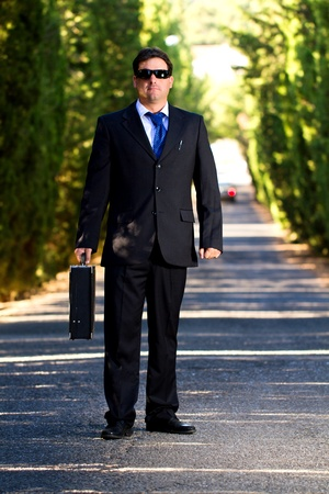 View of a young male business man on a asphalt road. photo