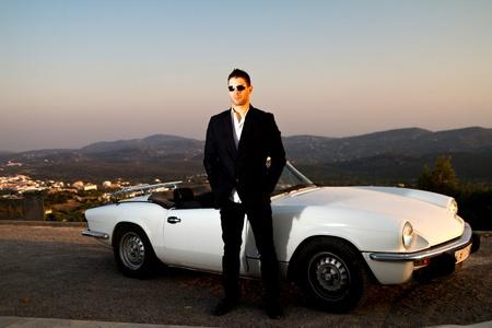 그의 옆에 흰색 컨버터블 자동차에 재킷을 가진 젊은 남성의 전망. 에디토리얼