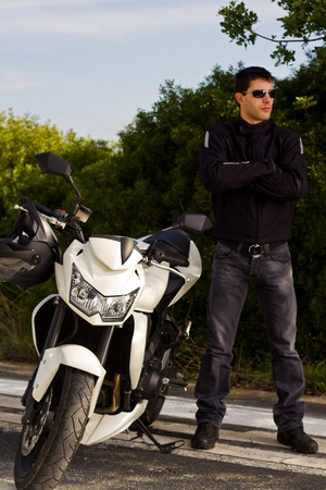 View of a man with a motorcycle on a asphalt road. photo