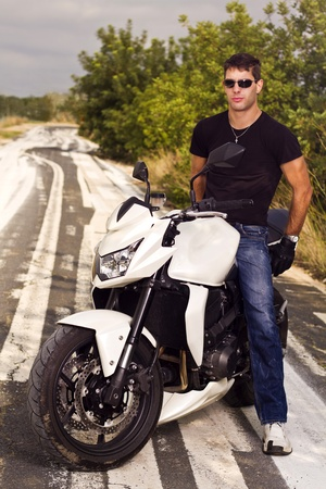 travel gear: View of a man with a motorcycle on a asphalt road.