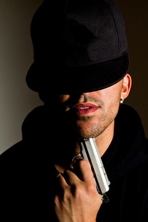 Close view detail of a man with a gun pointing to his chin.