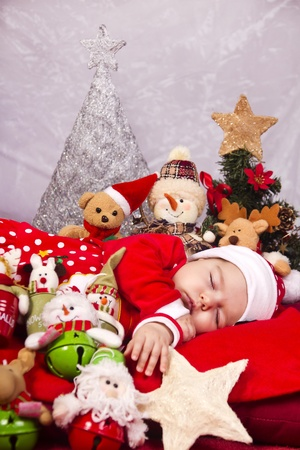 View of a newborn baby on a Christmas suit with stuffed toy. photo