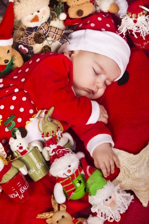 View of a newborn baby on a Christmas suit sleeping. photo