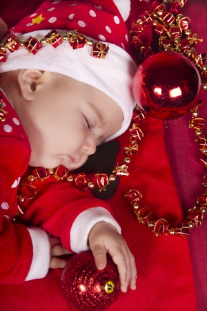 View of a newborn baby on a Christmas suit sleeping.