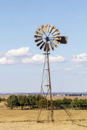 portugal agriculture: Close view of an old water pumping windmill on a dry land. Stock Photo