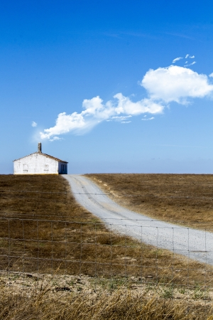 View of a conceptual photo with a lonely house with road on a dry land with white clouds exiting the chimney. photo