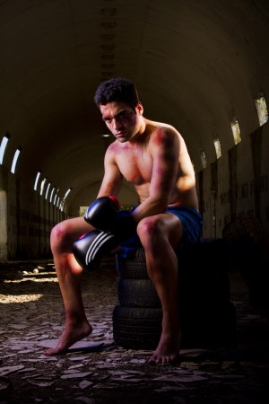 blood sport: View of a wounded fighter with blood stains on a abandoned factory.