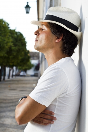 mediterranean style: View of a handsome man with white shirt and hat on a urban city.