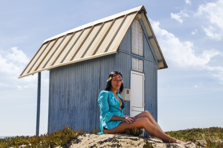 View of a beautiful woman in bikini in the beach, bathed by the sunny rays of Summer next to a blue wood house. photo