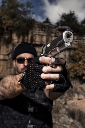 View of a man with dark shades pointing a gun to the camera. Stock Photo - 17497575