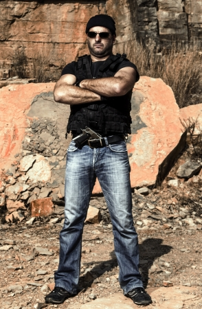 View of a man with a gun in jeans and jacket on a stone quarry. photo