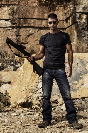 gun man: View of a man with a shotgun in jeans and black shirt on a stone quarry. Stock Photo
