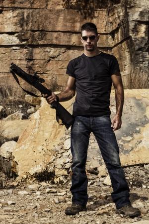 de maras: Vista de un hombre con una escopeta en pantalones vaqueros y la camisa negra en una cantera de piedra. Foto de archivo
