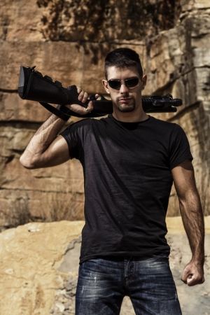 View of a man with a shotgun in jeans and black shirt on a stone quarry. Stock Photo