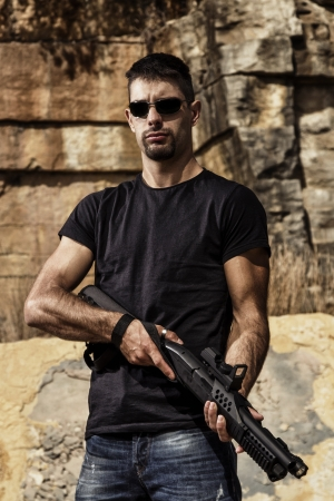 View of a man with a shotgun in jeans and black shirt on a stone quarry. photo