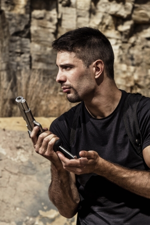 View of a menacing man reloading a handgun in a black shirt and dark shades on a stone quarry.