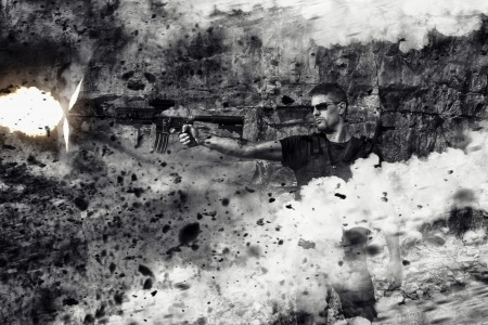 muzzle flash: View of a menacing man firing a machine gun in an action scene with explosions on a stone quarry. Stock Photo