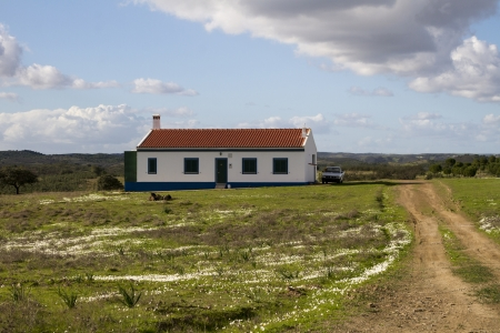 portuguese: Landscape view of a traditional house with dirt road on the countryside of Alentejo.