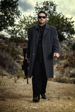 View of a contracted type killer agent wandering with a long jacket and machine gun. Stock Photo - 17528371