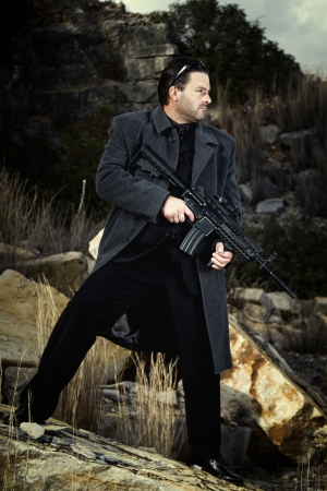View of a contracted type killer agent wandering with a long jacket and machine gun. Stock Photo - 17497628