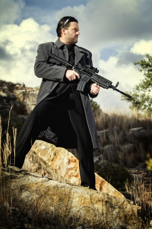 View of a contracted type killer agent wandering with a long jacket and machine gun. Stock Photo - 17498118