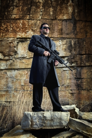 View of a contracted type killer agent wandering with a long jacket and machine gun. Stock Photo - 17528351