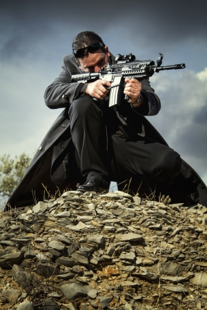 View of a contracted type killer agent wandering with a long jacket and machine gun. Stock Photo - 17498263