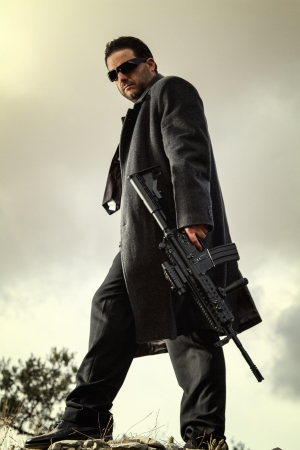 View of a contracted type killer agent wandering with a long jacket and machine gun. Stock Photo - 17497579