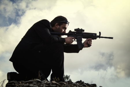 View of a contracted type killer agent wandering with a long jacket and machine gun. Stock Photo - 17496072