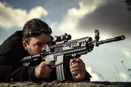 View of a contracted type killer agent wandering with a long jacket and machine gun. Stock Photo - 17496466