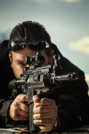 contracted: View of a contracted type killer agent wandering with a long jacket and machine gun.