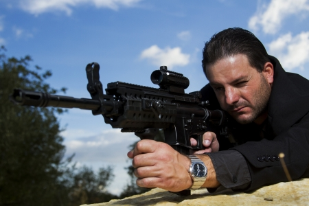 View of a contracted type killer agent wandering with a long jacket and machine gun. Stock Photo - 17496099