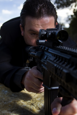 View of a contracted type killer agent wandering with a long jacket and machine gun. Stock Photo - 17496102