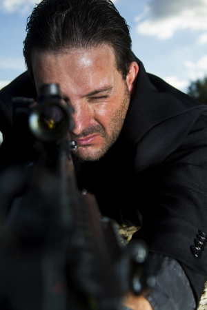 View of a contracted type killer agent wandering with a long jacket and machine gun. Stock Photo - 17492746