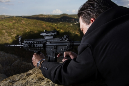 View of a contracted type killer agent wandering with a long jacket and machine gun. Stock Photo - 17496073