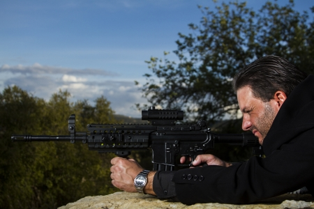 View of a contracted type killer agent wandering with a long jacket and machine gun. Stock Photo - 17496218