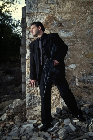 View of a contracted type killer agent wandering with a jacket and machine gun. Stock Photo - 17497618