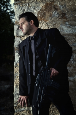 View of a contracted type killer agent wandering with a jacket and machine gun. Stock Photo - 17496016