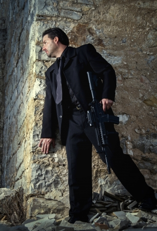 View of a contracted type killer agent wandering with a jacket and machine gun. Stock Photo - 17496461