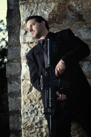 contracted: View of a contracted type killer agent wandering with a jacket and machine gun.