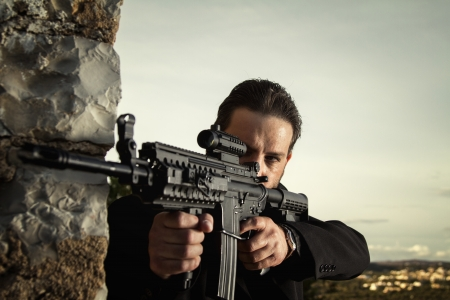 View of a contracted type killer agent wandering with a jacket and machine gun. Stock Photo - 17496149