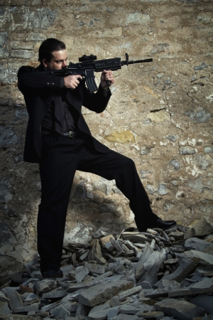 contracted: View of a contracted type killer agent wandering with a  jacket and machine gun. Stock Photo