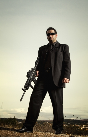 View of a contracted type killer agent wandering with a jacket and machine gun. Stock Photo - 17492546